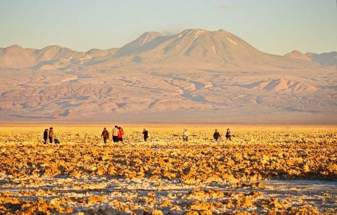 """People walking the paths through the salt flats in the Atacama Desert"""